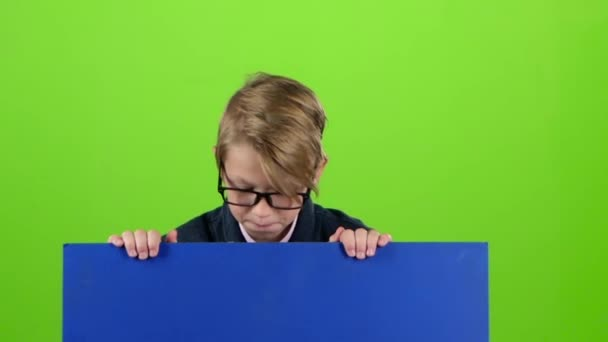 Dítě chlapec s brýlemi vypadá zpod desky, drží ji na zelené obrazovce. Zpomalený pohyb