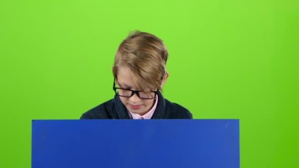 Dítě chlapec s brýlemi dostane nahoru a ukazuje na tabuli na zelené obrazovce. Zpomalený pohyb
