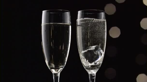 Dvě flétny šampaňského s transparentní kusů ledu na dně. Bokeh blikající černé pozadí. Detailní záběr