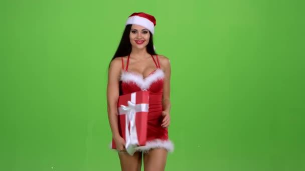 Egy új év-ruha lány egy ajándék tartja a kezében. Zöld képernyő. Lassú mozgás
