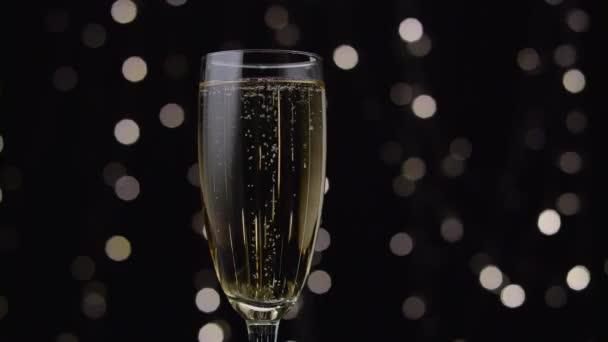 Glas Champagner mit einer rotierenden Blase im Inneren. Bokeh-Hintergrund