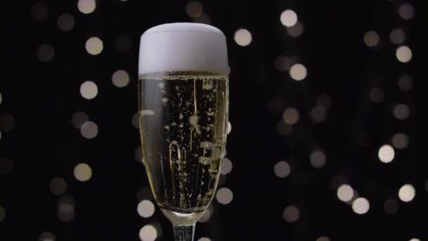 Champagne vylévá bílé pěny přes okraje skla. Bokeh pozadí