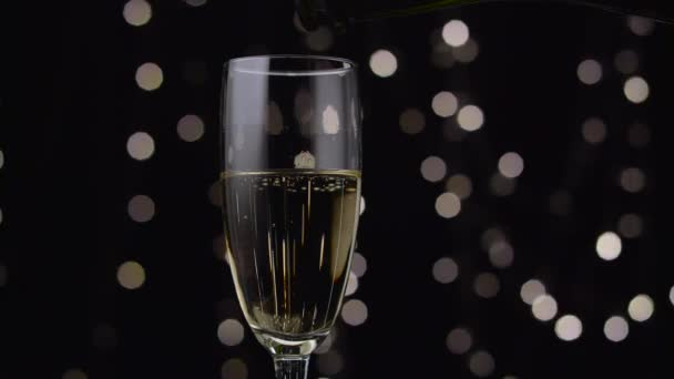 Šampaňské se nalije do sklenice. Bokeh pozadí