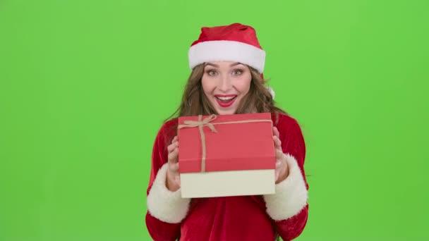 Egy snow maiden ruha lány egy ajándék tartja a kezében. Zöld képernyő. Közelről. Lassú mozgás