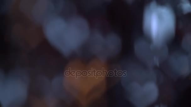 Jasné blikající světla proti ve tvaru srdce na černé obrazovce. Bokeh pozadí