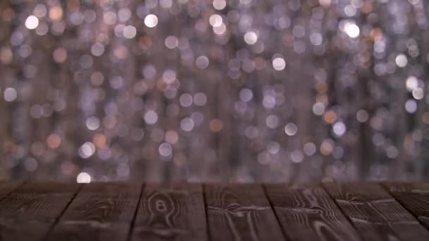 Fából készült asztal a képernyőn a csillogó absztrakt homályos színes körök. Háttérben a bokeh
