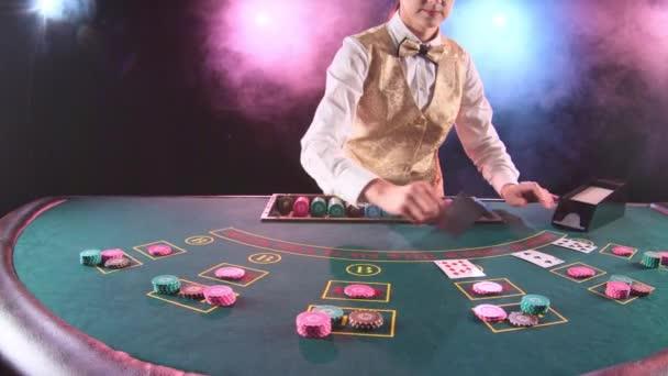 Kasino Stickman Frau in gold Weste nimmt die Karten vom Karteninhaber für Spiel im Poker. Schwarzer Hintergrund. Rauch. Slow-motion