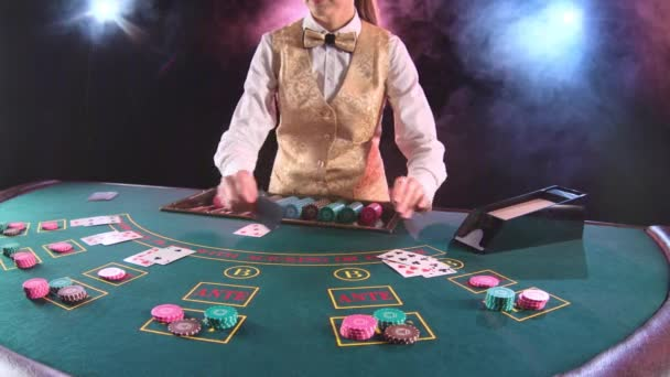 Kasino Stickman Frau in gold Weste nimmt die Karten vom Karteninhaber am Spieltisch. Schwarzer Hintergrund. Rauch. Slow-motion