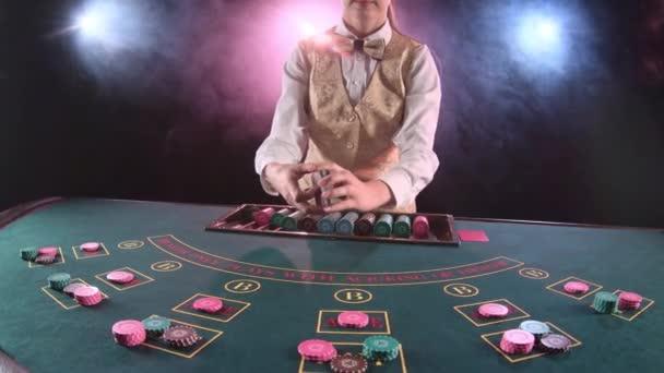 Kasino Stickman Frau verteilt Karten auf der Poker-Tischplatte. Schwarzer Hintergrund. Rauch. Slow-motion