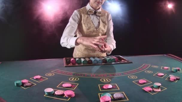 Kasino Stickman Frau verteilt Karten auf der Poker-Tischplatte mit geschnittenen Karte. Schwarzer Hintergrund. Rauch. Slow-motion