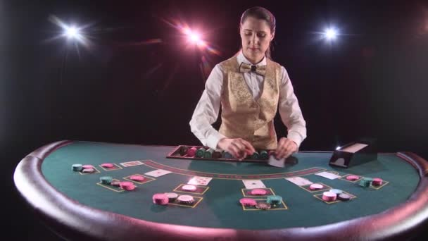 Casino dealer zpracování hrací karty u pokerového stolu. Černé pozadí. Zpomalený pohyb