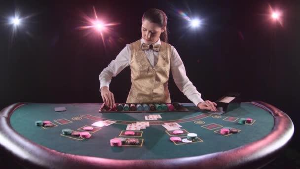 Casino dealer vytáhne boty karty stanoví chips u pokerového stolu. Černé pozadí. Zpomalený pohyb