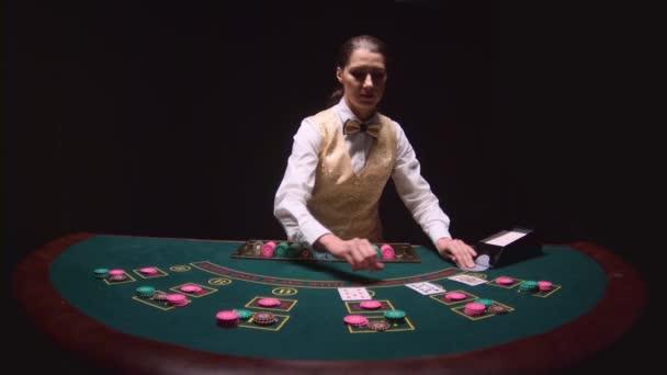 Casino dealer táhne karty od držitele karty, stanoví bramborové lupínky u pokerového stolu. Černé pozadí. Zpomalený pohyb