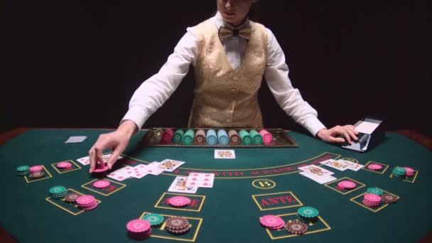 Croupier di poker mescola carte da gioco smazzante fuori il mazzo sul tavolo. Sfondo nero. Slow motion