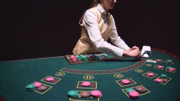 Croupier donna casinò prende le carte dal titolare della carta al tavolo da gioco. Sfondo nero. Slow motion