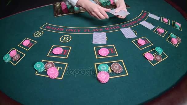 Krupiér kasinu distribuuje karty. Zpomalený pohyb. Detailní záběr
