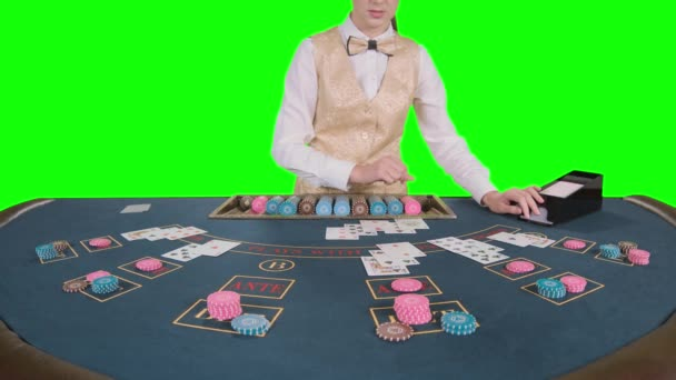 Kasino krupiérských dívka stojící na kostky stolu bere karty od držitele karty pro hry v poker. Zelená obrazovka. Zpomalený pohyb