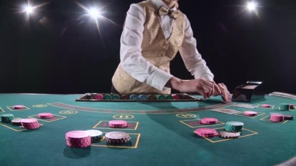 Casino-Stickman in gold Weste nimmt die Karten vom Karteninhaber am Spieltisch. Schwarzer Hintergrund. Helles Licht. Slow-motion