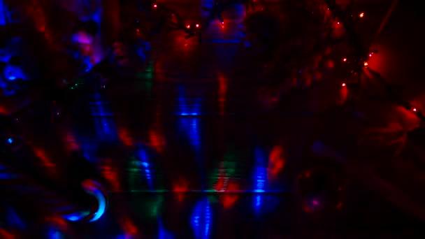 Camera oscura, ghirlande sono in fiamme, sulla tabella si trova una caramella e giocattoli nuovi anni. Vista dallalto