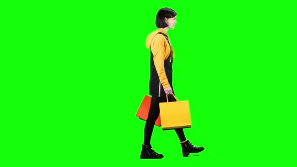 Dospívající dívka s balíčky je na ulici. Zelená obrazovka. Boční pohled