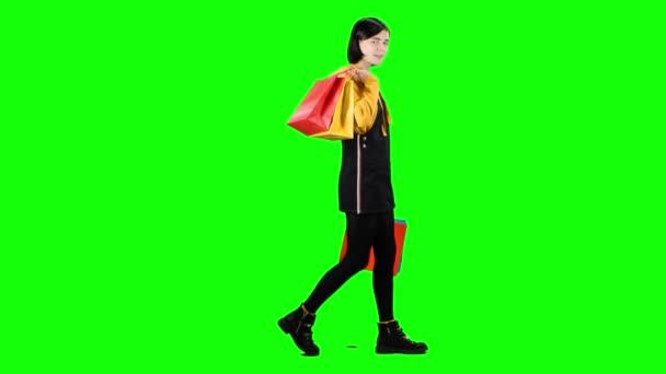 Mädchen mit Paketen läuft die Straße hinunter. Green Screen. Seitenansicht