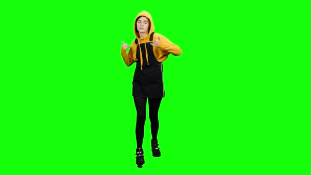 Girl walks and grimaces. Green screen