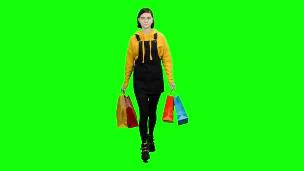 Dívka chodí po ulici s balíčky v jejích rukou. Zelená obrazovka