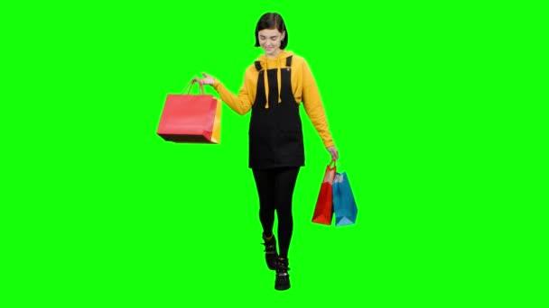 Teen je chůze po ulici s balíčky v dlaních. Zelená obrazovka
