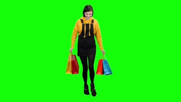 Mädchen mit Taschen in der Hand nach dem Einkauf ist glücklich einkaufen. Green Screen