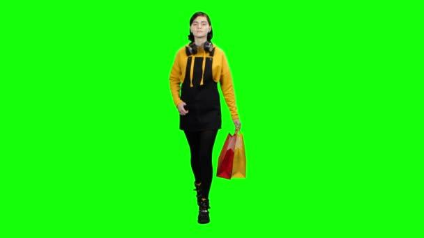 Teen jde s balíčky po nakupování a rozhlíží. Zelená obrazovka