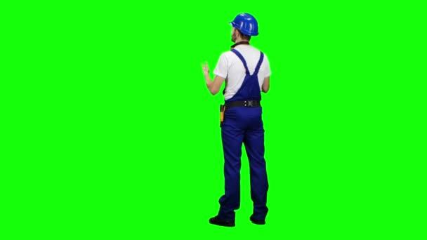 Stavitel stojí zády a něco řekne. Zelená obrazovka. Pohled zezadu