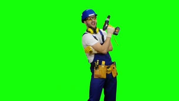 Arbeiter mit Schutzbrille und Bohrer in der Hand. Green Screen