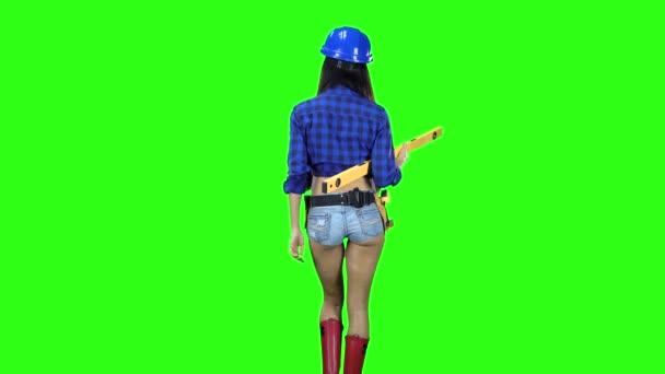 Pohled zezadu na dívku v helmě a šortky s úrovní v ruce chůzi na zeleném pozadí