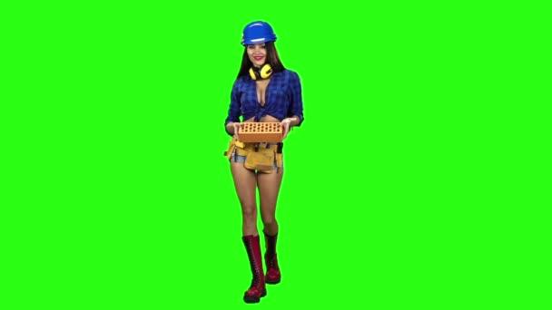 Dívka v kraťasech s cihel jde na zeleném pozadí. Zpomalený pohyb