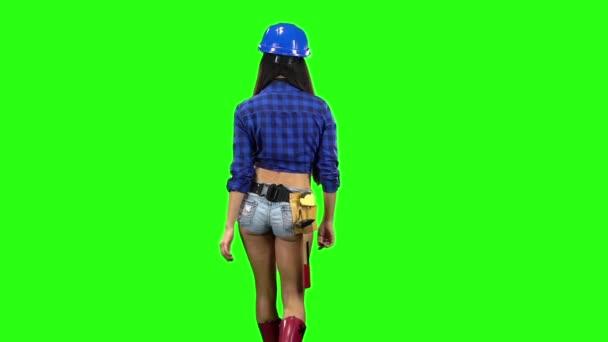 Pohled zezadu na dívka, která nosí helmu a šortky na zeleném pozadí. Zpomalený pohyb