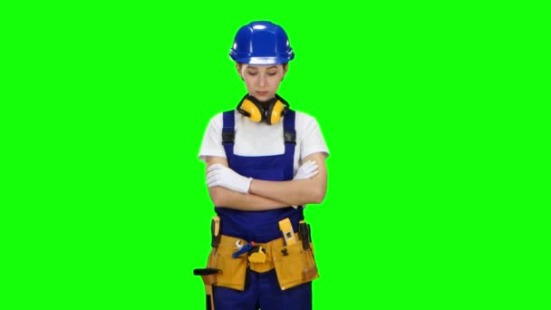Builder girl in the helmet raises her head and starts to smile. Green screen