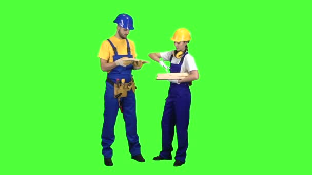 Pair of builders choose wooden boards. Green screen. Slow motion