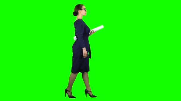 Designerin kommt mit einer Zeichnung in der Hand. Green Screen. Seitenansicht