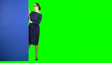 Girl peeks out and points at the billboard. Green screen