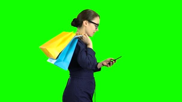 Dívka v brýlích vytočí zprávy na telefonu a jde do obchodu, je v dobré náladě z nakupování. Zelená obrazovka