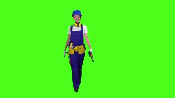 Brigádní dívka přichází s vrtačkou v ruce. Zelená obrazovka. Zpomalený pohyb