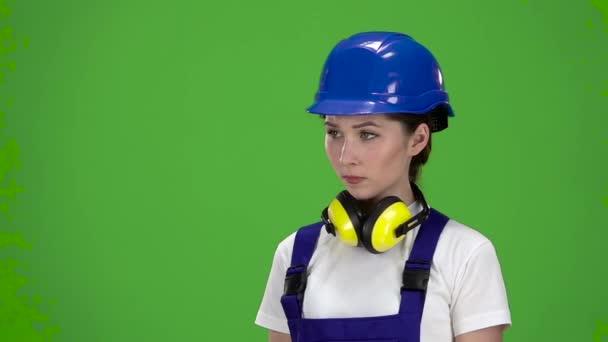 Inženýr dívka v přilbu a kombinézu drží vrtačku v jejích rukou. Zelená obrazovka. Zpomalený pohyb. Detailní záběr