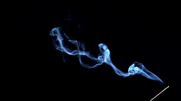 Vonné tyčinky jsou pálení a kouře na černém pozadí, kouř z kadidla. Zpomalený pohyb