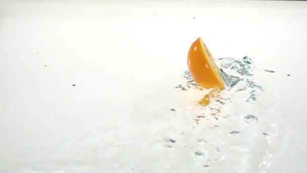 Půl orangedrops do vody. Bílé pozadí. Zpomalený pohyb