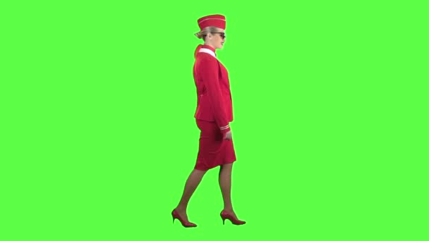 Girl walks and waves, she is a flight attendant in a red suit and a cap. Green screen. Side view. Slow motion