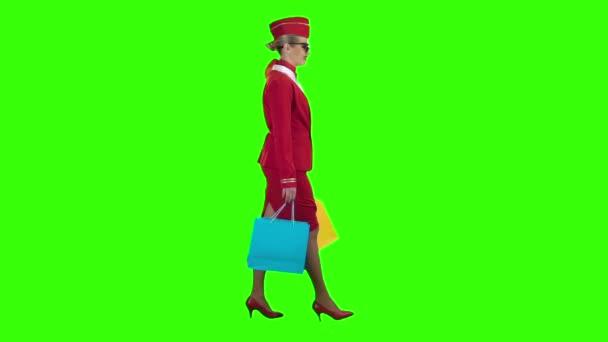 Dívka v sluneční brýle je přichází s nákupní tašky. Zelená obrazovka. Boční pohled. Zpomalený pohyb
