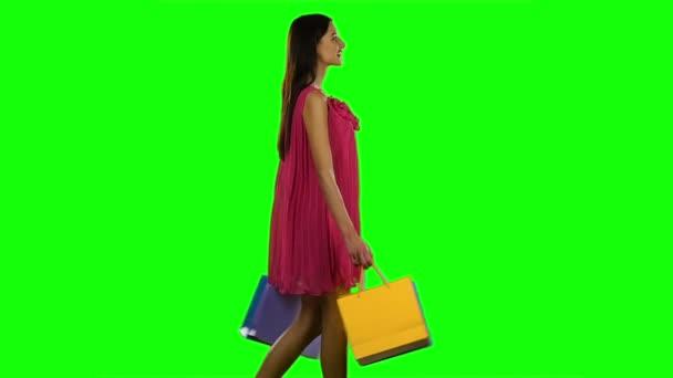 Pörgő gyönyörű nő. Bevásárlótáska a kezében és sétál. Zöld vászon. Lassú mozgás.