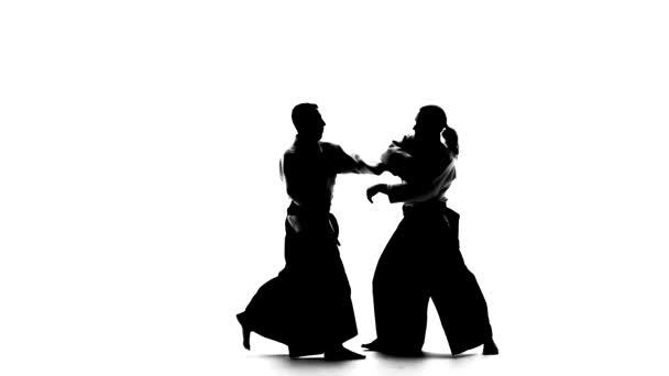 schwarze Silhouetten von zwei Männern in Keikogi oder Kimono, die Aikido-Techniken demonstrieren. isoliert, weiß. Zeitlupe.