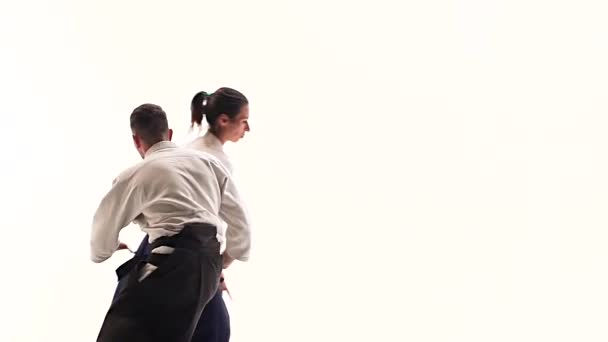 Man and woman in white keikogi showing aikido techniques, isolated on white. Close up. Slow motion.