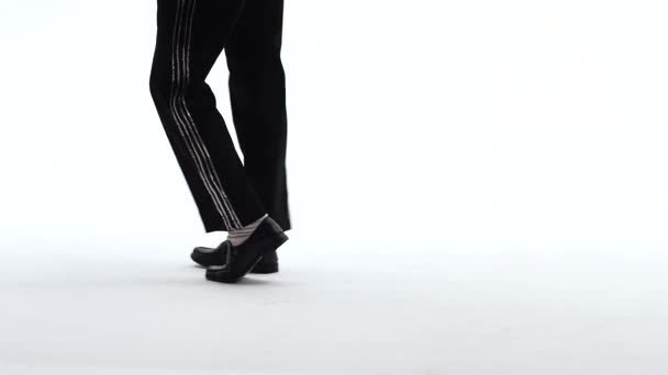 Young stylish teenager is showing dance moves like Michael Jackson. Isolated over white background. Close up of legs, slow motion.